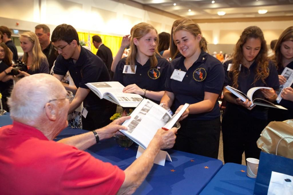 Brenna Leech, a senior, recieves an autograph from one of the veterans interviewed by VHP. The VHP reception was held to honor those involved in the making of its book.