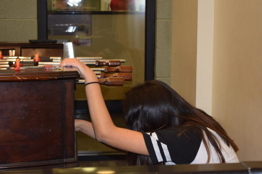 Melanie Matzen angrily getting the ball to continue playing foosball.
