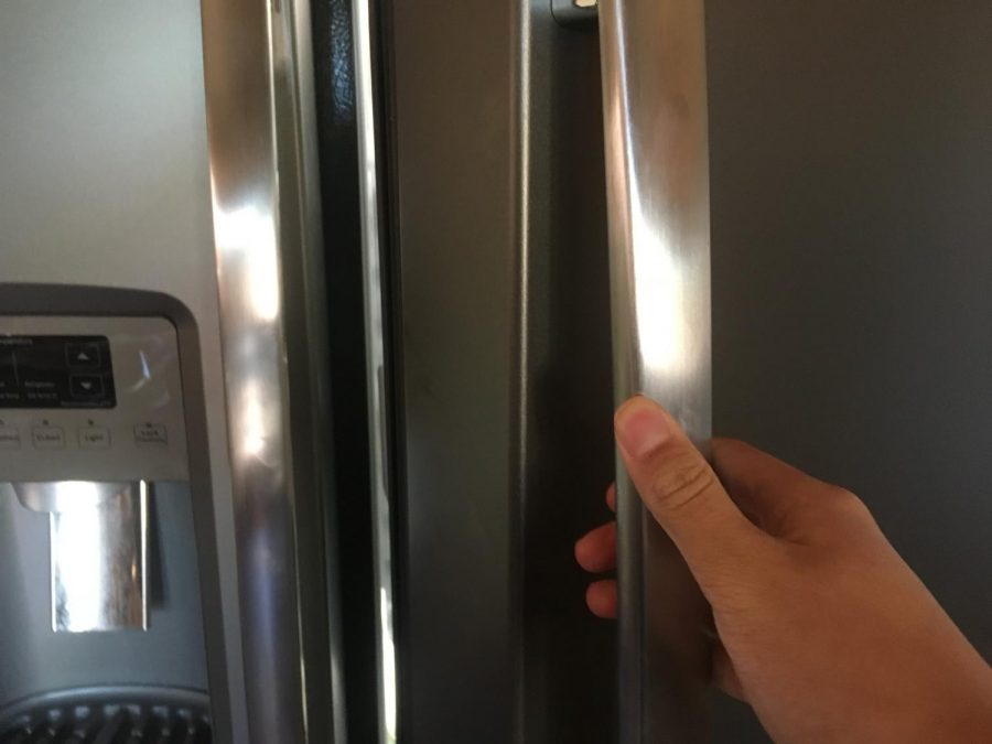 A student opens the fridge to get food.