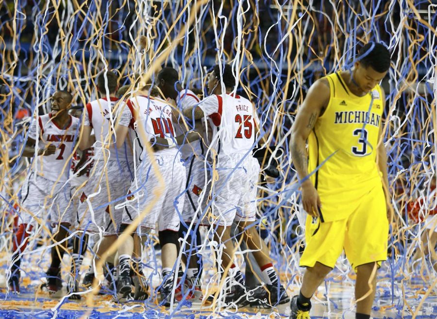 Michigan Wolverines guard Trey Burke (3) walks off the court as the Louisville Cardinals celebrate defeating Michigan to win the NCAA men's Final Four championship basketball game in Atlanta, Georgia April 8, 2013.   REUTERS/Jeff Haynes (UNITED STATES  - Tags: SPORT BASKETBALL TPX IMAGES OF THE DAY)   ORG XMIT: ATL159