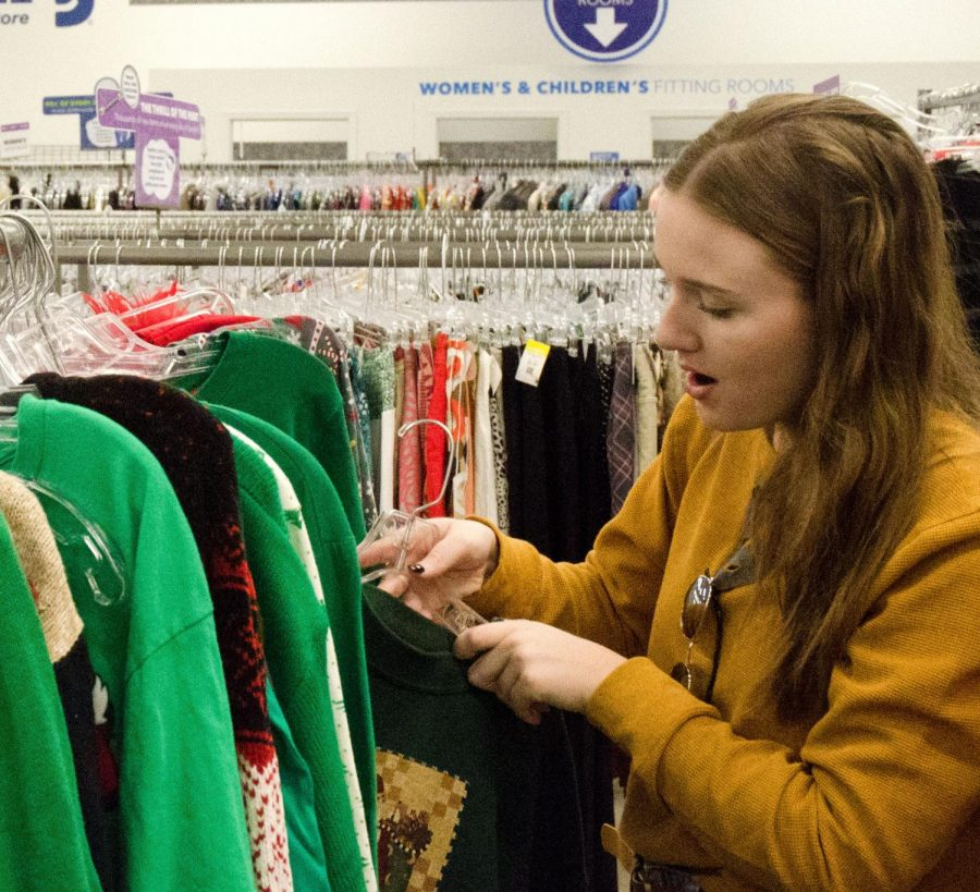 Karli Kinsey, a junior, sifts through countless racks of Christmas clothing at Goodwill.