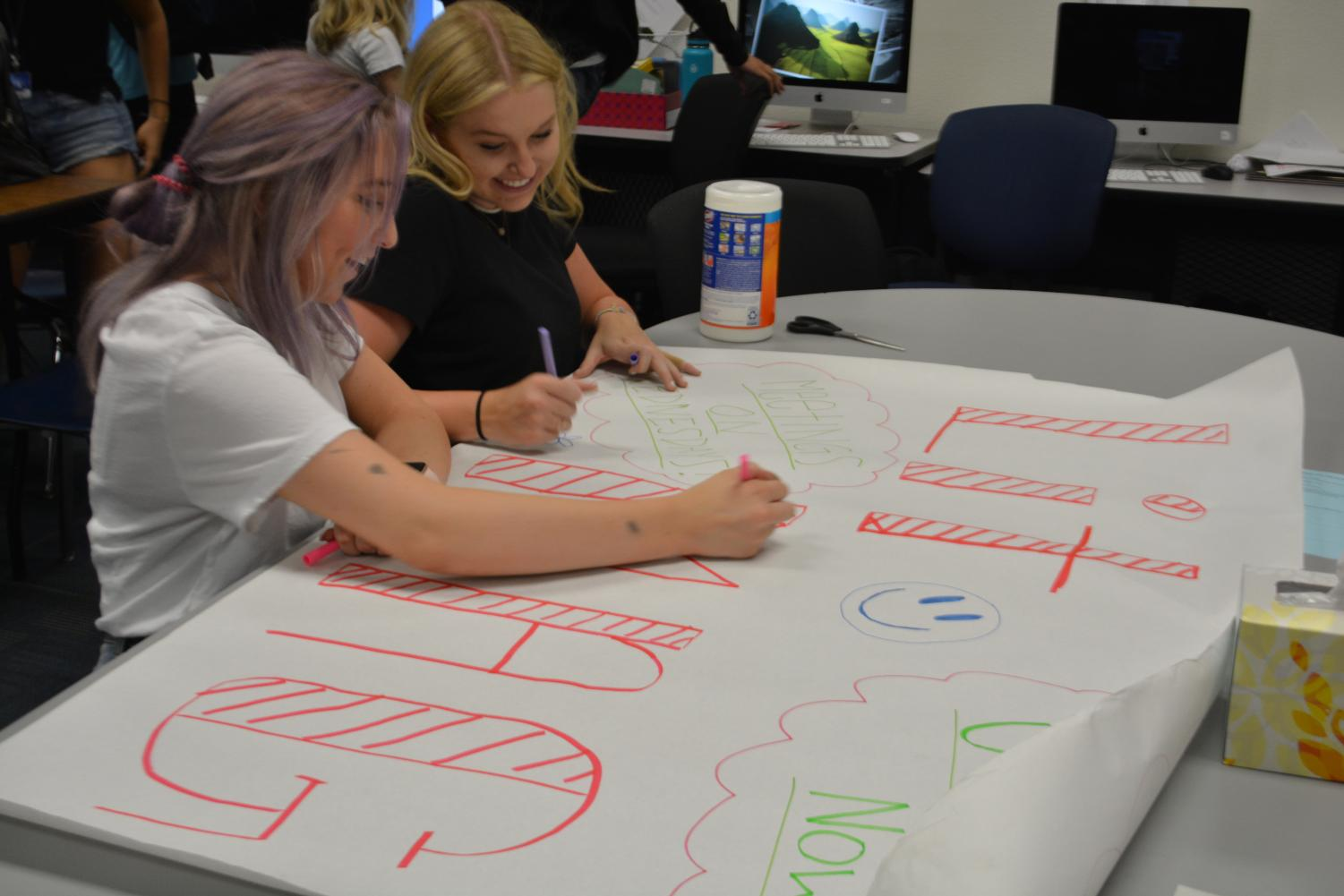 Lola Draper and Mikki Warriner work on advertisement for the club.