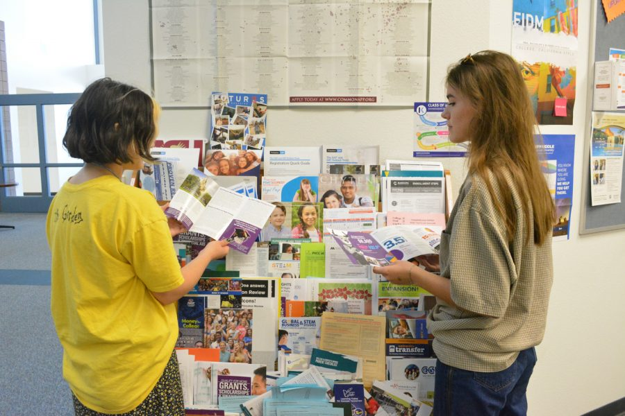 Applying to colleges and scholarships can be stressful for students. Greer Greenberg and Kamryn Bartkus, juniors, consider colleges by reading pamphlets that the counselors provide.