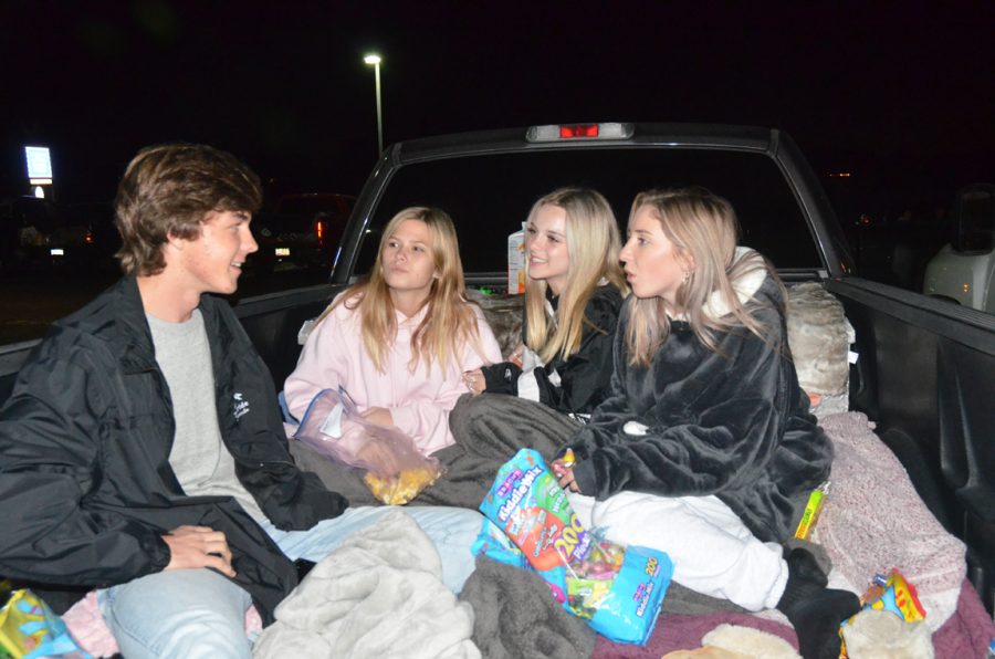 """Seniors Ali Cahanes, Abigail Querrey, Lola Draper and Nathan Granger hanging at Truck Or Treat Tailgate Party out before the movie started. """"I thought it was really fun, I liked being in the trucks and how movie night was done this year,"""" said Cahanes."""