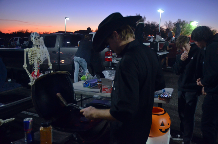 """Seth Martian, a senior, cooking some burgers and hot dogs for Truck or Treat Tailgate Party. """"I love getting the opportunity to cook at these events, it's nice getting to see everyone have a good time,"""" said Martin."""