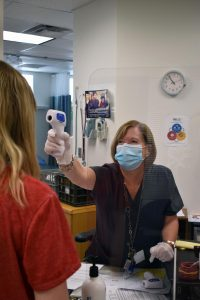 Doreen Decker, Health Assistant, takes a student