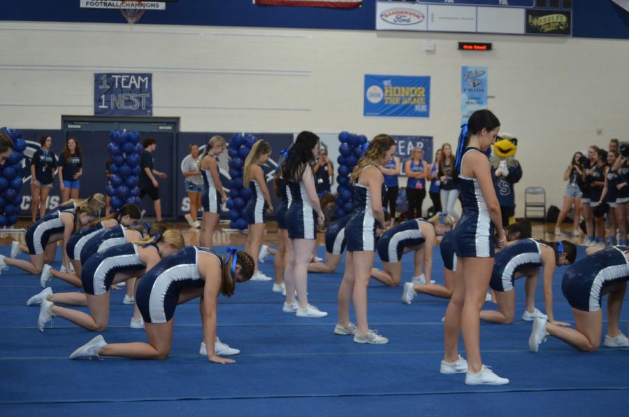 Cheering in the Year: Varsity Cheer prepares to perform their first routine of the school year. The team has been practicing the routine since the beginning of august.